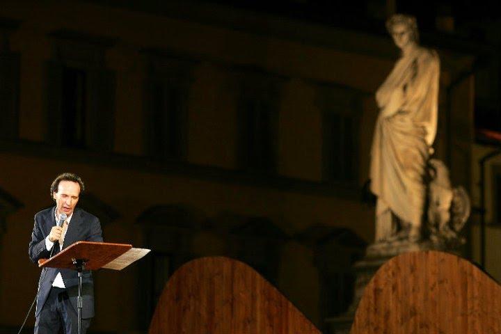 Benigni recitando con la escultura de Dante al fondo